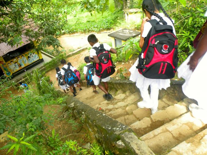 Sri Lankan students make the steep climb down from their primary school, which served as a school kit distribution site. Children in this community were affected by landslides after flooding monsoon rains.