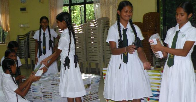 Secondary school girls form a chain to efficiently move and pack notebooks for flood-affected Sri Lankan students.
